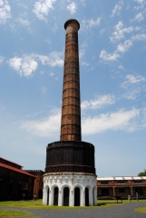 """Smokestack: """"Completed in 1855, this 125 foot chimney was used to draw smoke from the Blacksmith Shop and Boiler Room via underground tunnels. In addition, the lower portion of the stack held a 40,000 gallon cast iron rain water collection tank and the small rooms under the tank served as prices and showers."""""""